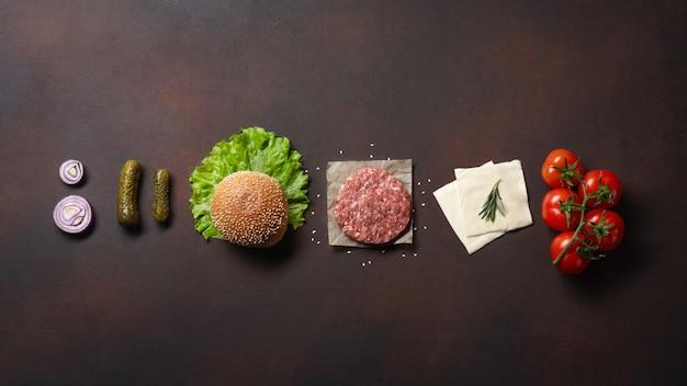 Hamburger di ingredienti cotoletta cruda, pomodori, lattuga, panino, formaggio, cetrioli e cipolla Foto Premium
