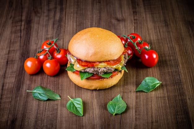 Hamburger di manzo artigianale con formaggio, peperoni italiani, pomodoro e foglie di basilico sul tavolo di legno Foto Premium
