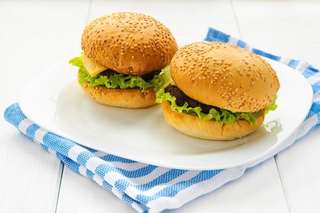 Hamburger di manzo fatti in casa sul piatto e tovagliolo. sfondo bianco in legno Foto Premium