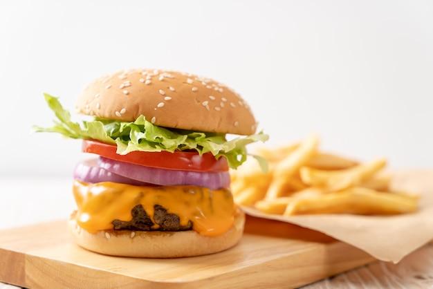 Hamburger di manzo fresco gustoso con formaggio e patatine fritte Foto Premium