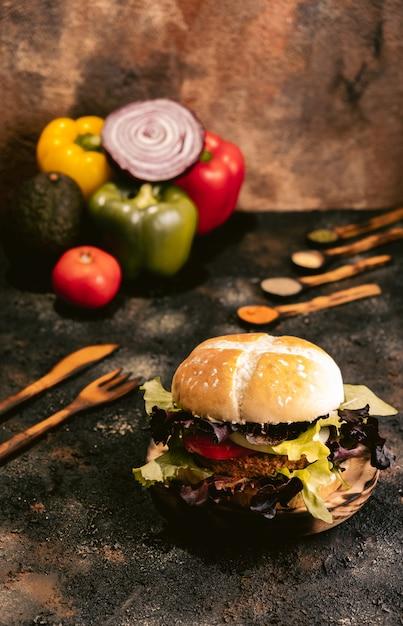 Hamburger di seitan vegan su superficie di legno con verdure. cibo vegano sano Foto Premium