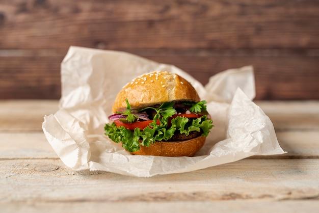 Hamburger di vista frontale con fondo di legno Foto Gratuite