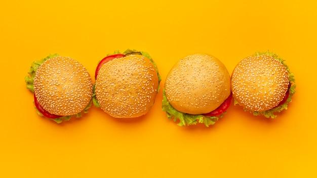 Hamburger di vista superiore con sfondo arancione Foto Gratuite