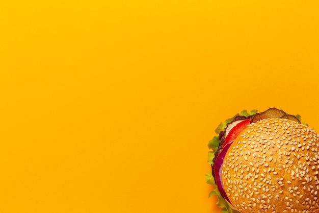 Hamburger di vista superiore su sfondo arancione Foto Gratuite