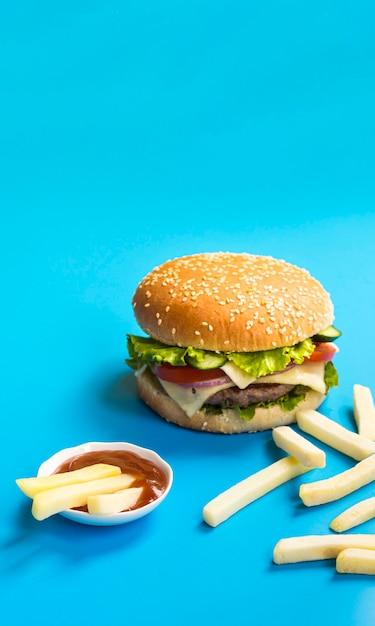 Hamburger e patate fritte su fondo blu Foto Gratuite