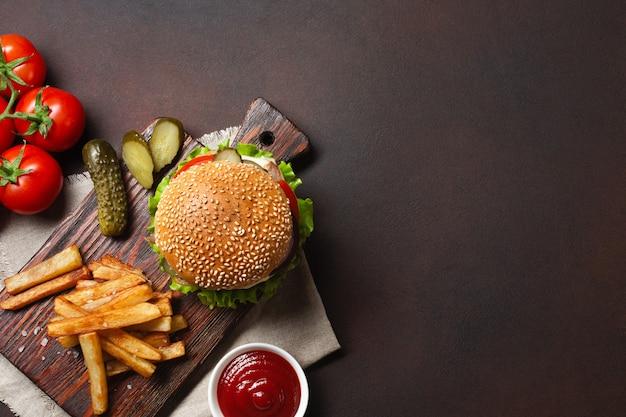 Hamburger fatti in casa con ingredienti di manzo, pomodori, lattuga, formaggio, cipolla, cetrioli e patatine fritte sul tagliere e sfondo arrugginito Foto Premium
