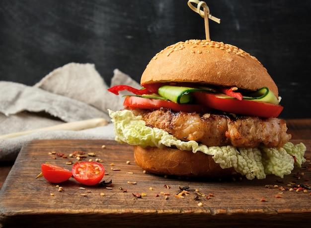 Hamburger fatto in casa con bistecca fritta di maiale, pomodori rossi, panino rotondo fresco con semi di sesamo Foto Premium