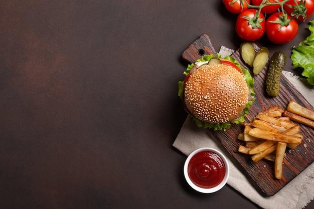 Hamburger fatto in casa con ingredienti di manzo, pomodori, lattuga, formaggio, cipolla, cetrioli e patatine fritte Foto Premium