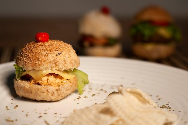 Hamburger gourmet con pomodoro, formaggio, pollo, manzo - sandwich naturale Foto Premium