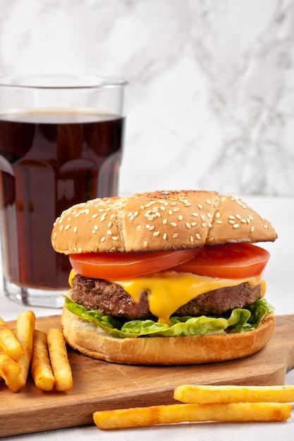 Hamburger gustoso fresco con formaggio, pomodoro e insalata con patatine fritte e cola Foto Premium