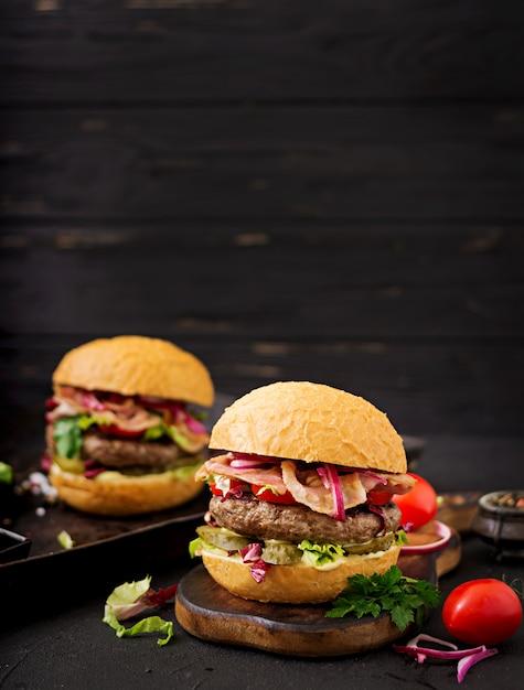 Hamburger hamburger con carne di manzo, pomodoro, cetriolo sottaceto e pancetta fritta. Foto Gratuite