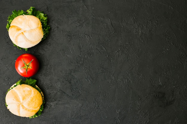 Hamburger piatto-lay su ardesia con copyspace Foto Gratuite