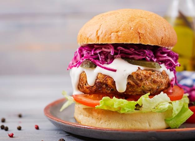 Hamburger sandwich con hamburger succosi, pomodoro e cavolo rosso Foto Premium