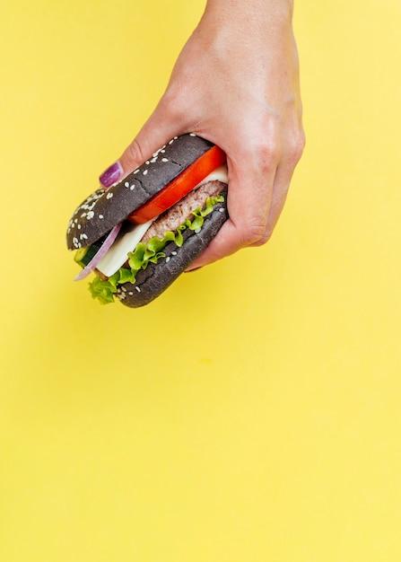 Hamburger tenuto di fronte a sfondo giallo Foto Gratuite