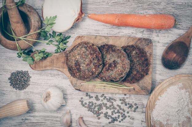 Hamburger vegano con lenticchie piatto vegano sano fondo in legno Foto Premium