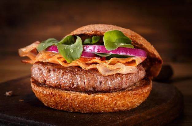Hamburger vicino su un tagliere su fondo di legno. Foto Premium