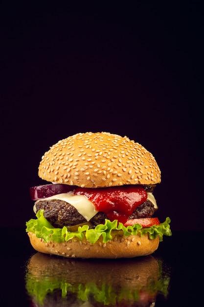 Hamburger vista frontale con sfondo nero Foto Gratuite