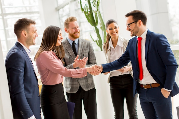 Handshaking dei partner commerciali dopo aver stretto un accordo con i dipendenti nelle vicinanze Foto Premium