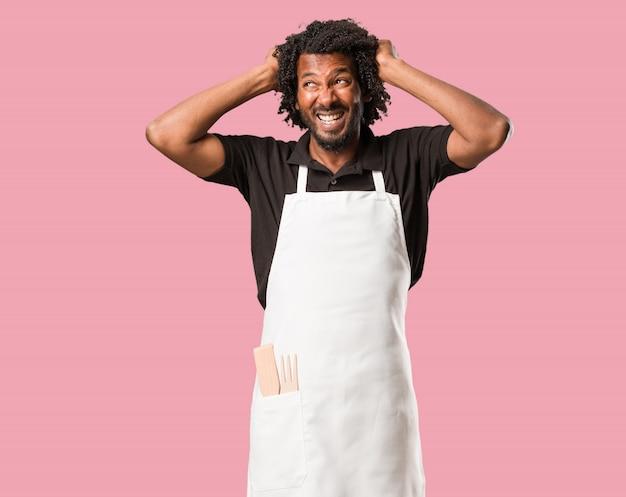 Handsome african american baker pazzo e disperato, urlando fuori controllo Foto Premium