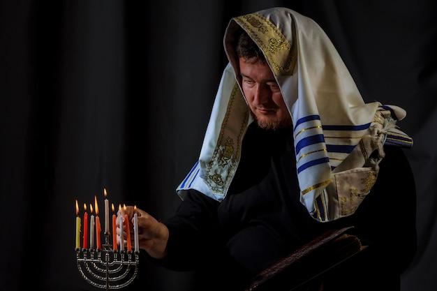 Hanukkah, una celebrazione ebraica. candele accese nella menorah, uomo sullo sfondo. Foto Premium