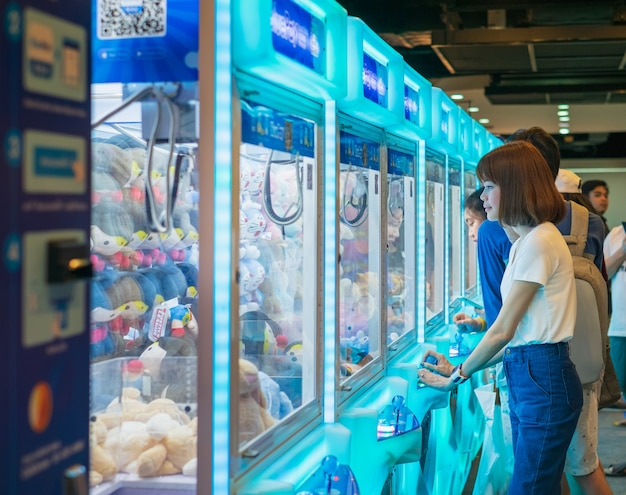 Happiness woman playing artw game or cabinet to catch the dolls Foto Premium