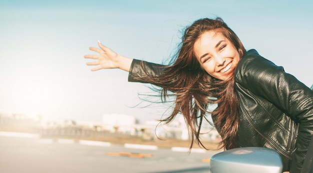 Happpy bella affascinante bruna capelli lunghi giovane donna asiatica in giacca di pelle nera in auto Foto Premium