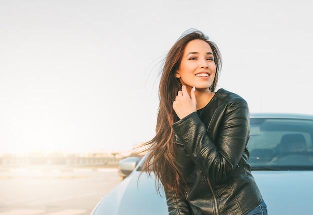 Happpy bella affascinante bruna capelli lunghi giovane donna asiatica in giacca di pelle nera vicino alla sua auto Foto Premium