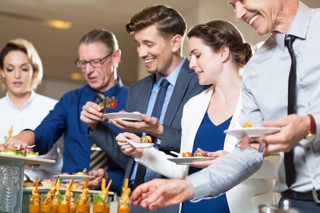 Happy business people per se stessi, a buffet Foto Gratuite
