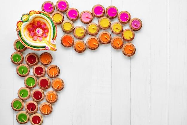 Happy diwali - le lampade di clay diya si sono accese durante il dipavali, festival indù della celebrazione delle luci. diya tradizionale variopinto della lampada a olio su fondo di legno bianco Foto Premium