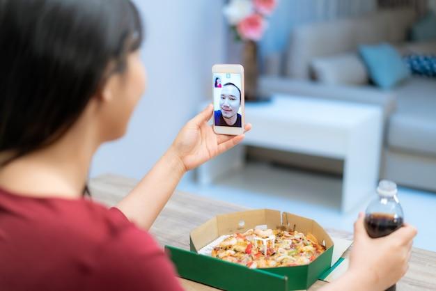 Happy hour virtuale della donna asiatica che incontra la cena e che mangia l'alimento della pizza online insieme al suo ragazzo nella videoconferenza con la compressa digitale Foto Premium
