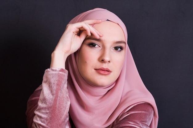 Hijab d'uso della giovane donna musulmana davanti a superficie nera Foto Gratuite