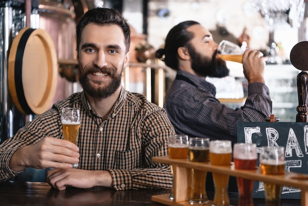 Hipsters have tasty craft beer microbrewery pub. Foto Premium