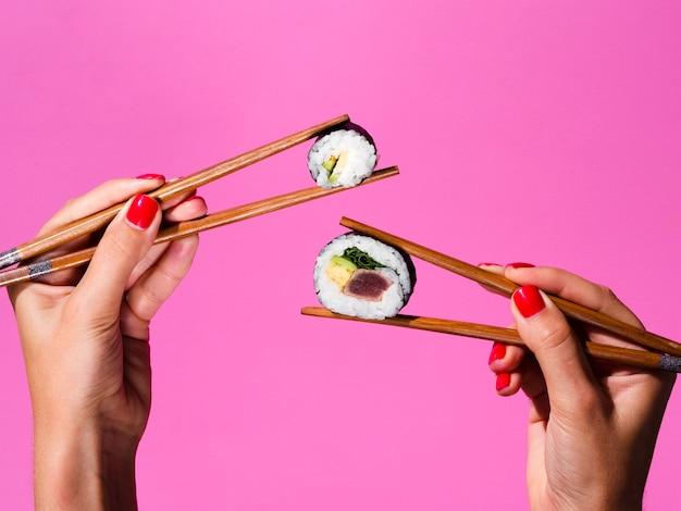 Holding della donna con entrambi i rotoli di sushi della mano sulle bacchette Foto Gratuite