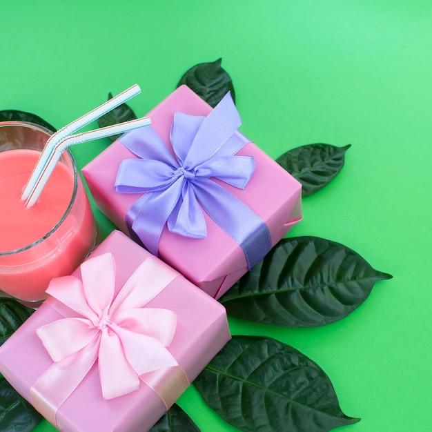 Holiday poster scatole con regali un bicchiere di milkshake uno sfondo verde brillante. Foto Premium
