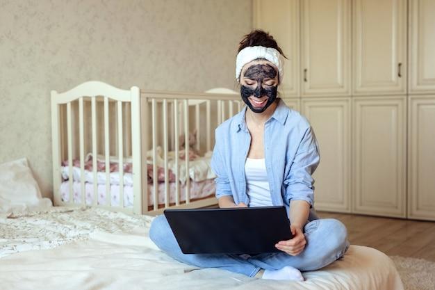 Home-office e ragazza indipendente in abiti domestici da una maschera di carbone sul viso lavora seduto a casa sul letto. Foto Premium