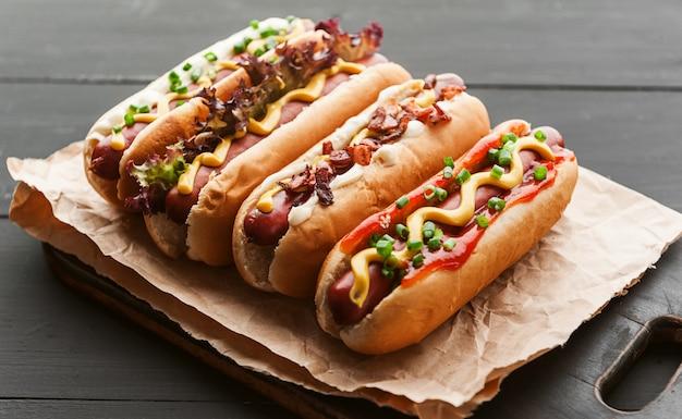 Hot dog alla griglia con senape americana gialla, su uno sfondo di legno scuro Foto Premium