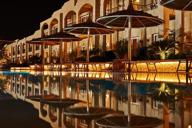 Hotel illuminato con piscina di notte. luci serali al resort Foto Premium