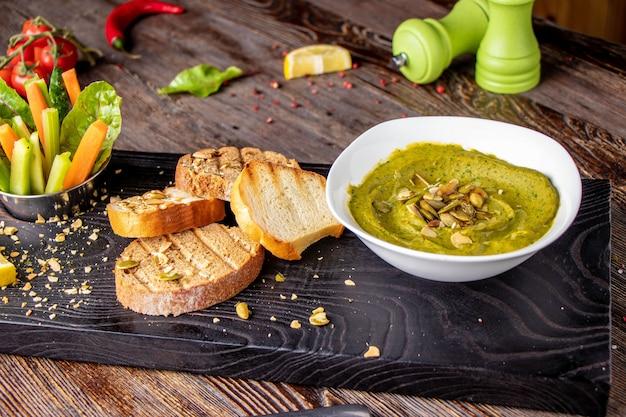 Hummus con spinaci, avocado e semi di zucca in una ciotola su una tavola di legno e bruschetta, cucina orientale Foto Premium