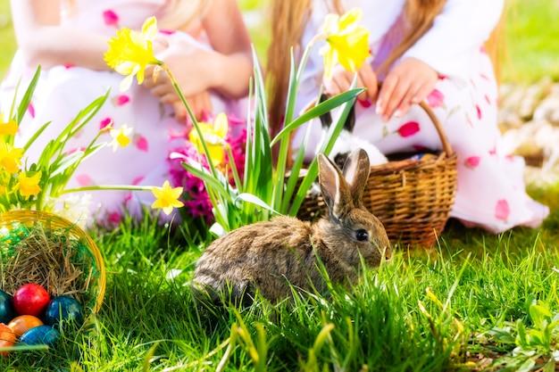 I bambini a caccia di uova di pasqua con coniglietto Foto Premium