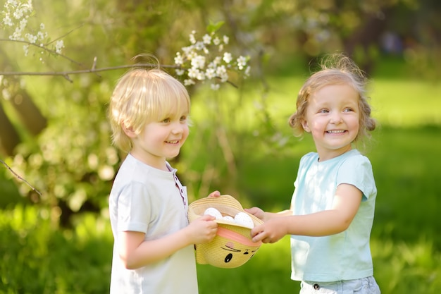 I bambini affascinanti cacciano per le uova dipinte nel parco di primavera il giorno di pasqua. Foto Premium