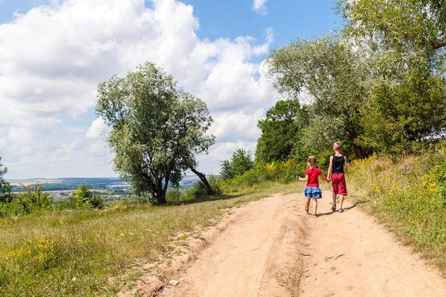 I bambini camminano su una strada sterrata Foto Premium