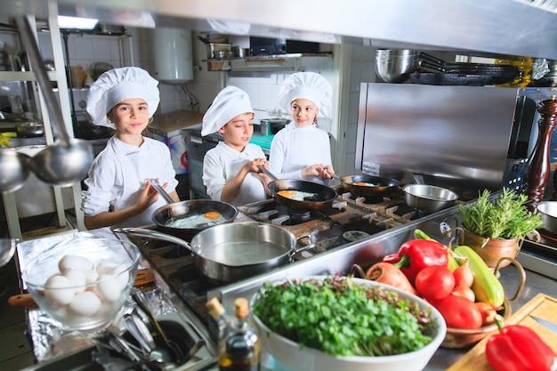 I bambini cucinano il pranzo in una cucina del ristorante. Foto Premium