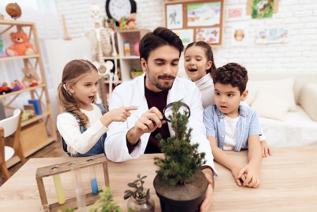 I bambini dell'asilo guardano sotto la lente d'ingrandimento Foto Premium