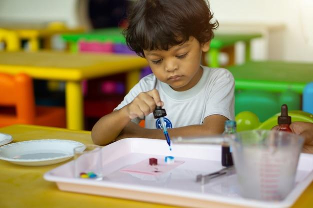 I bambini di 3 anni in asia conducono esperimenti scientifici. Foto Premium