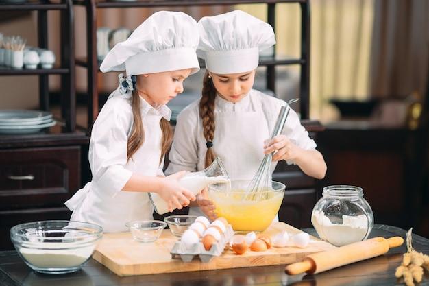 I bambini divertenti delle ragazze stanno preparando l'impasto in cucina. Foto Premium