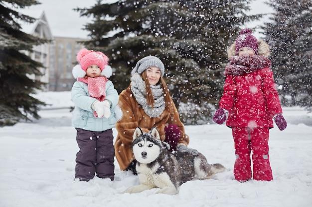 I bambini escono e giocano con il cane husky in inverno. i bambini si siedono sulla neve e accarezzarono il cane husky. passeggiata nel parco in inverno, gioia e divertimento, cane husky con gli occhi blu. russia, sverdlovsk, Foto Premium