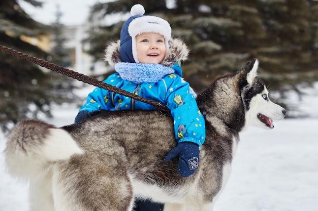 I bambini escono e giocano con il cane husky in inverno. Foto Premium