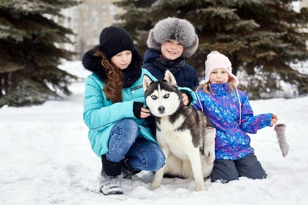 I bambini escono e giocano con il cane husky in inverno Foto Premium