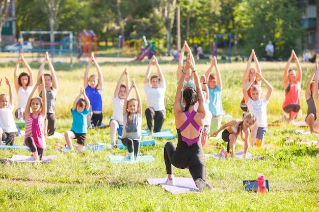 I bambini fanno yoga con un allenatore all'aperto. Foto Premium