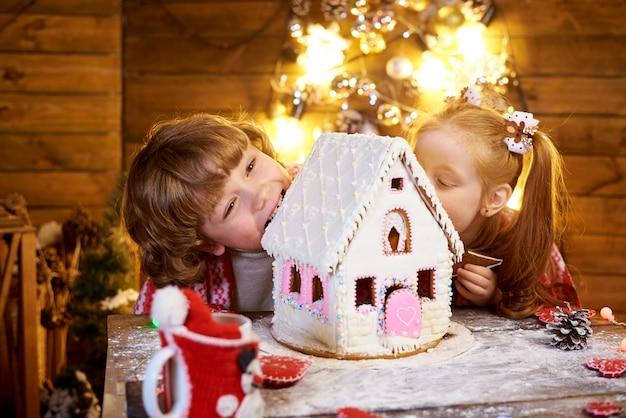 I bambini felici mordono il pan di zenzero di natale in una stanza decorata per le vacanze. Foto Premium